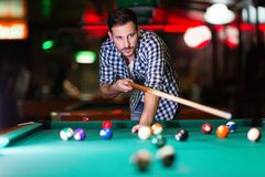 Hansome man playing pool in bar alone. Aiming Stock Photography