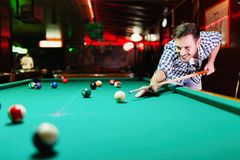 Hansome man playing pool in bar alone. Aiming Stock Photo