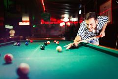 Hansome man playing pool in bar alone. Aiming Stock Photos