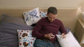 Hansome man som använder den smarta telefonen, medan ligga i säng på natten lager videofilmer