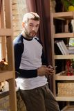 Hansome man standing by the window at home. Sexy young male at home interiror, holding phone in hands Stock Image