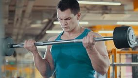 Hansome muscular man raises the bar in the gym. Close up Royalty Free Stock Photos