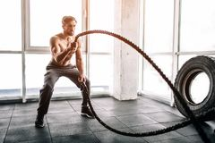 Hansome and well-built man is doing some exercises with waving two big and thick ropes one after another. This exercise. Hansome and well-built men is doing some Royalty Free Stock Photos