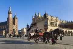 Hansomtaxi på gammal stadfyrkant i Krakow, Polen. Royaltyfri Fotografi