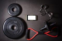 Hantel och skivstång, smartphone, färdig livåtlöje upp, livsstil Arkivbilder