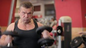 Hantlar i idrottshallen - muskelutbildning Mannen lyfter hantlar i idrottshallen Nakacheny de stora mandreven med hantlar stock video