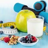 Hantlar med sund mat på blå bakgrund Fotografering för Bildbyråer