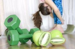 Hantlar, nya gröna frukter och kvinnan som gör sträckning, poserar Begrepp av sunt och sportigt liv arkivfoton