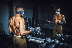 Hantlar och arbete för idrotts- man för afrikansk amerikan lyftande på hans biceps framme av spegeln på idrottshallen svart man i Royaltyfria Foton