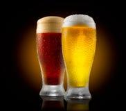 Hantverköl Två exponeringsglas av kallt ljus och mörkt öl som isoleras på svart arkivbilder