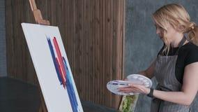 Hantverk av målning Kameran flyttar sig runt om de nätta kvinnliga konstnärerna, medan hon målar en abstrakt bild med stora slagl royaltyfri illustrationer