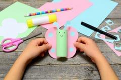 Hantverk för fjäril för barninnehavpapper i händer Barnet visar roliga pappers- hantverk Brevpapper på en gammal trätabell royaltyfri fotografi