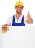 Hantverkare bak det blanka tecknet som visar upp tum Royaltyfria Bilder