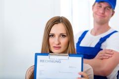 Hantverkare eller rörmokare som ger den overpriced fakturan Arkivfoto