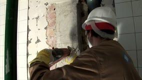 Hantverkare som arbetar med elektrisk rivning som gå i flisor hammaren arkivfilmer