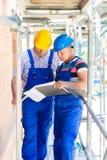 Hantverkare som kontrollerar plan för byggnadsplats eller konstruktions Royaltyfri Foto