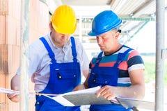 Hantverkare som kontrollerar plan för byggnadsplats eller konstruktions Royaltyfri Fotografi