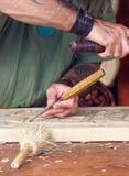 Hantverkare som snider en souvenir från trä Arkivfoton