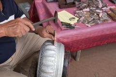 hantverkare som snider lotusblommakronbladmodellen på en metallbunke Arkivfoto
