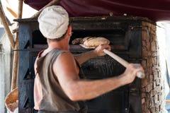 Hantverkarebagare som introducerar produkten i den wood ugnen Arkivbilder