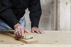 Hantverkarehand som sandpapprar ekträ Arkivfoton