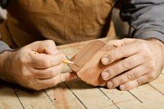 Hantverkarehänder som skissar på den wood kubben Royaltyfri Foto