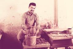 Hantverkaremannen som skapar det keramiska stycket på snurrkrukmakeri, rullar in royaltyfria bilder