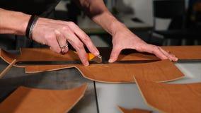 Hantverkaren är bitande ut stycken från stort läder, genom att använda regel och bladet arkivfilmer