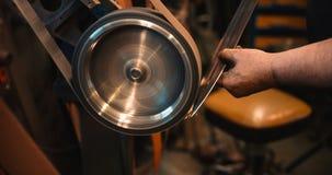 Hantverkaren använder en bälteslipmaskin i maskin shoppar Arkivbild