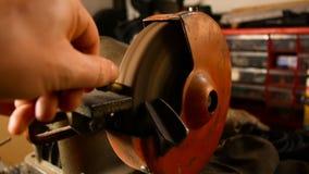 Hantverkaren använder ett elektriskt hjul för att mala en metallstång i hans hem- seminarium stock video
