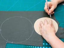 Hantverkaren drar klippmodellen genom att använda pappers- form royaltyfria bilder