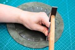 Hantverkaren gör hål i sydd påse vid stansmaskin arkivbild