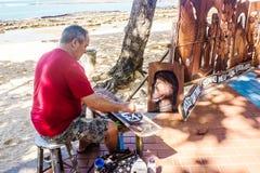 Hantverkaren Itamar som snider och säljer hans stycken vid havet i Guarapari, Brasilien royaltyfria foton