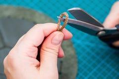 Hantverkaren klipper dragsnöret för påse vid sax royaltyfri fotografi
