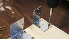 Hantverkaren skruvar upp skruvarna med en manuell elektrisk skruvmejsel arkivfilmer