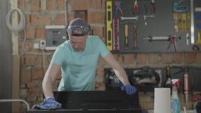 Hantverkarereflexion av den behandskade yttersidan för snickaretvagningspegel En man plaskar p? yttersidan av sprejen Begrepp lager videofilmer