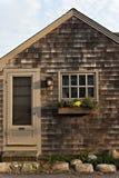 Hantverkarestilstuga med det wood singlar, fönstret och flowerbox Fotografering för Bildbyråer