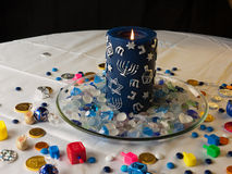 Candle and seasonal toys with Jewish elements. A traditional Jewish Hanuka candle, chocolate money and sweets on the white table cloths and the dreidels. White Royalty Free Stock Photography