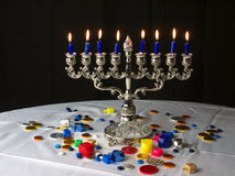 Hanuka lights. A traditional Jewish Hanuka menorah, with 9 candles. Chocolate money and sweets on the white table cloths and the dreidels Stock Photography