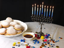 Hanuka lights and donuts. A traditional Jewish Hanuka menorah, with 9 candles. Jelly donuts, chocolate money and sweets on the white table cloths and the Stock Photo