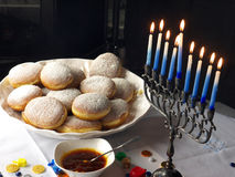 Hanuka lights and donuts. A traditional Jewish Hanuka menorah, with 9 candles. Jelly donuts, chocolate money and sweets on the white table cloths and the Royalty Free Stock Photography