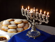 Hanuka lights and donuts. A traditional Jewish Hanuka menorah, with 9 candles. Jelly donuts white and blue table cloths Royalty Free Stock Image