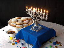 Hanuka lights and donuts. A traditional Jewish Hanuka menorah, with 9 candles. Jelly donuts white and blue table cloths Royalty Free Stock Photo