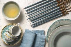 Hanukkah με τα κεριά, τα πιάτα, το βούτυρο σε ένα κύπελλο και την μπλε πετσέτα Στοκ φωτογραφίες με δικαίωμα ελεύθερης χρήσης