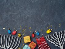 Hanukkah background. With menorah, gift box and dreidel over blackboard. View from above. Flat lay Stock Image