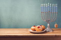 Hanukkah background with menorah and sufganiyot on wooden table Stock Images