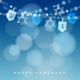 Hanukkah blue background with string of lights, dreidels and jewish stars. Stock Photos