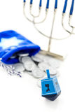 Hanukkah. Blue dreidel with silver tokens on a white background