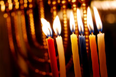 Hanukkah Candles. Brightly lit candles on the 6th night of Hanukkah with a brass menorah in the background stock image