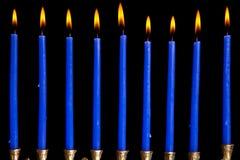 Hanukkah candles on black background. Burning hanukkah candles in a menorah on black background stock photo